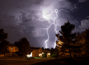 Lightning striking above a home on a dark night